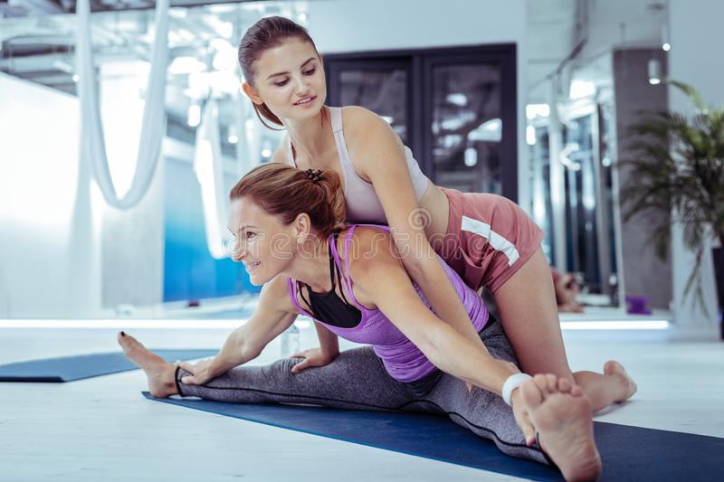 Experienced female trainer instructing yoga to woman royalty free stock photos