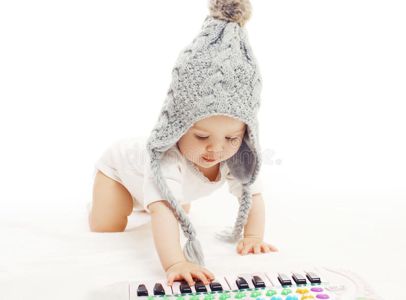Development child, baby in knitted hat playing stock photos