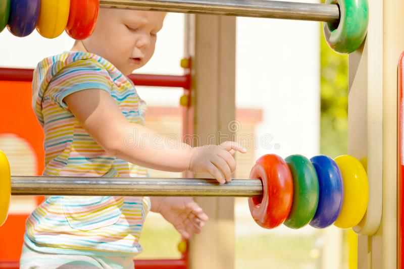 Development of fine motor skills and thinking in a child. A little girl in striped clothes playing with children`s plastic rings on the Playground. For the stock images