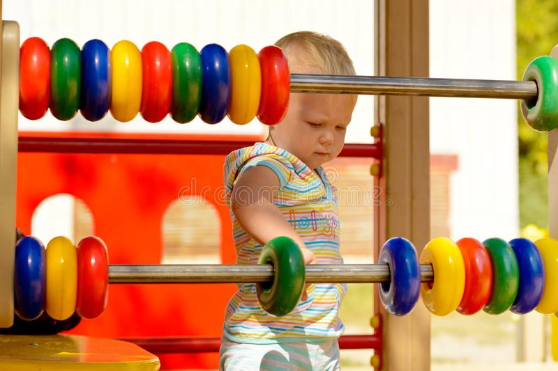 Development of fine motor skills and thinking in a child. A little girl in striped clothes playing with children`s plastic rings on the Playground. For the royalty free stock photography