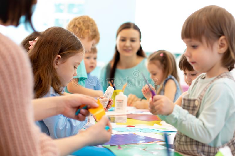 Development learning children in preschool. Children`s project in kindergarten. Group of kids and teacher cutting paper royalty free stock image
