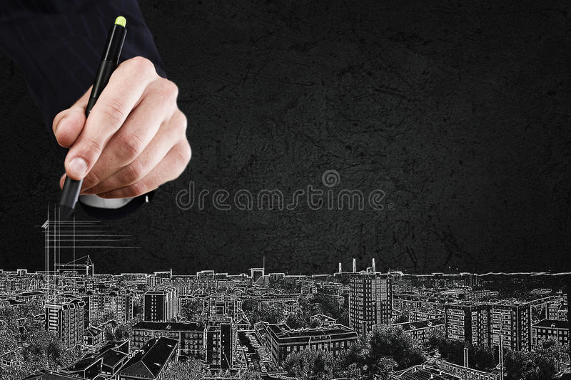 Development project. Close up of hand drawing urban city buildings royalty free stock photography