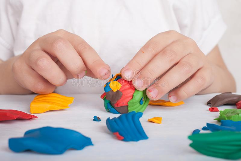 Development of small motor skills of children. A child sculpts a colorful ball of plasticine. Closeup macro, hands stock images