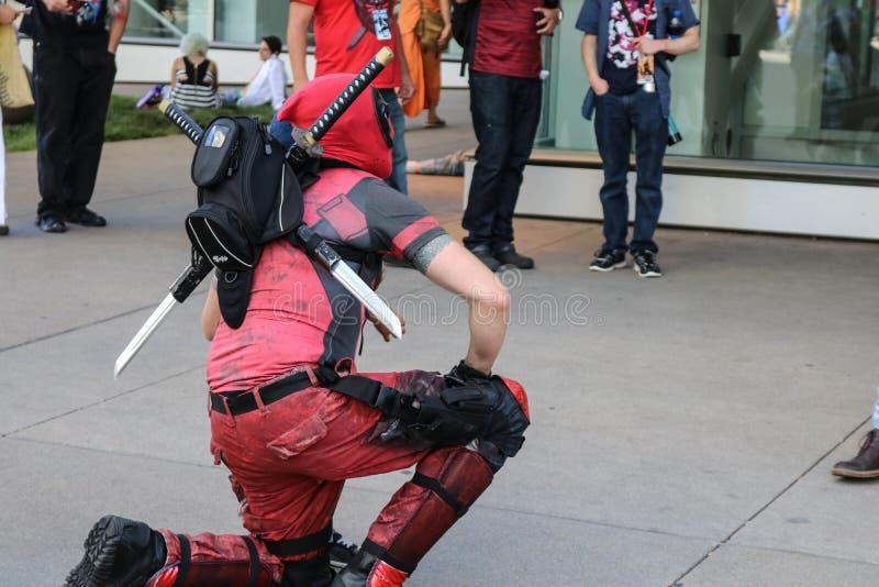 Dever Colorado, USA - Juli 1, 2017: Personen i den Deadpool dräkten knäfaller för ett foto på Denver Comic Con royaltyfri foto
