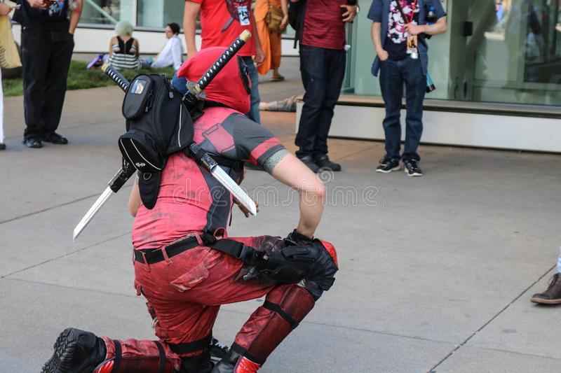 Dever, Colorado, USA - July 1, 2017: Person in Deadpool costume kneels for a photo at Denver Comic Con. Deadpool character in costume kneels down for a photo at royalty free stock photo