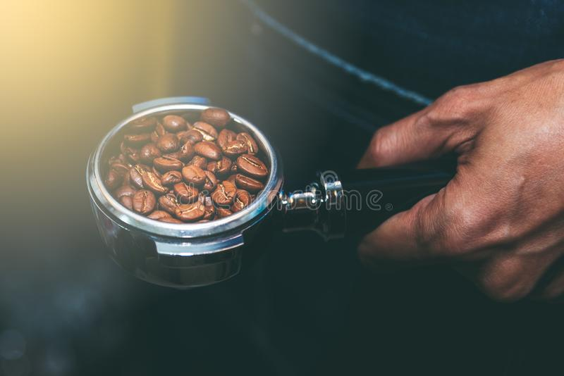 Device that contains coffee beans. The coffee maker holds a device that contains coffee beans, preparing coffee for customers royalty free stock photo