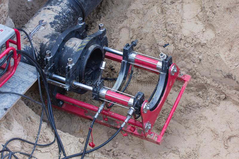 A device for welding plastic pipes. Is used at the construction site for laying external networks, pipes for supplying water supply royalty free stock photography