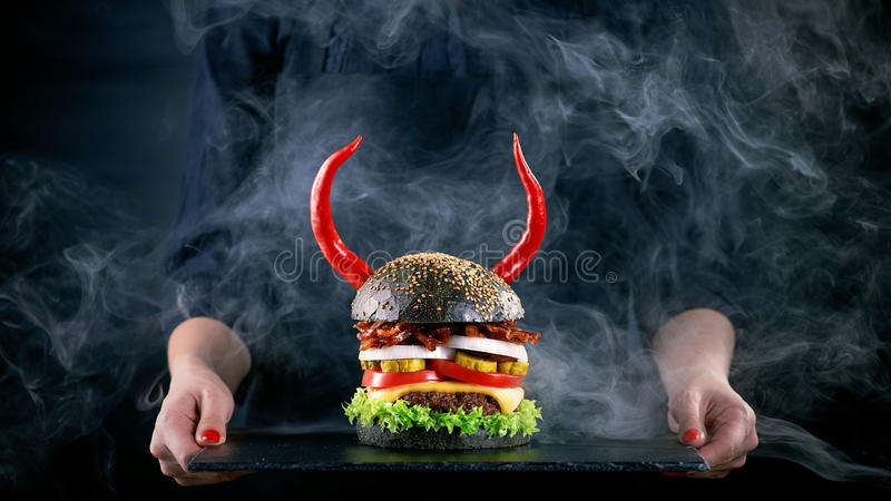 Devil burger with bacon and vegetables on black slat plate. In woman hands royalty free stock photo