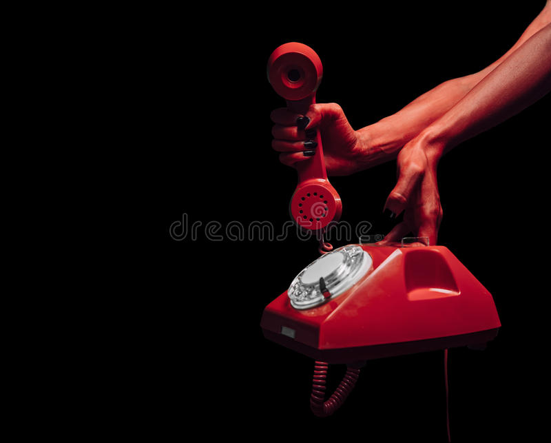 Devil hands with retro phone. Red devil hands giving retro phone on dark background, space for text, Halloween or horror theme stock image