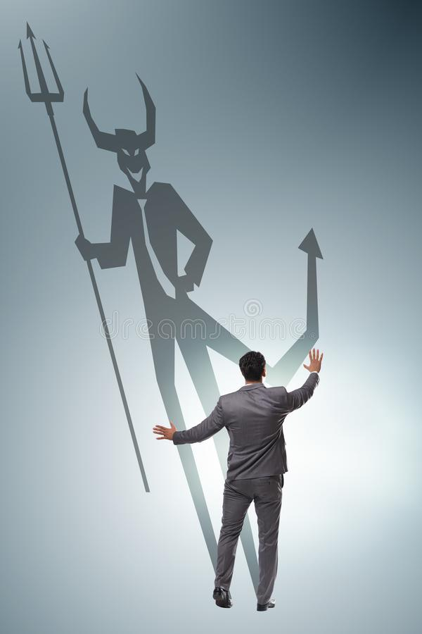 Devil hiding in the businessman - alter ego concept royalty free stock image