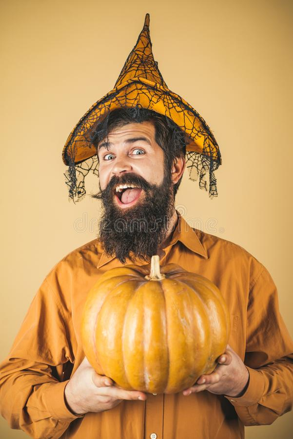 Devil man. Halloween man with pumpkin - Holidays celebration concept. Scary hipster man with beard in Halloween hat royalty free stock images