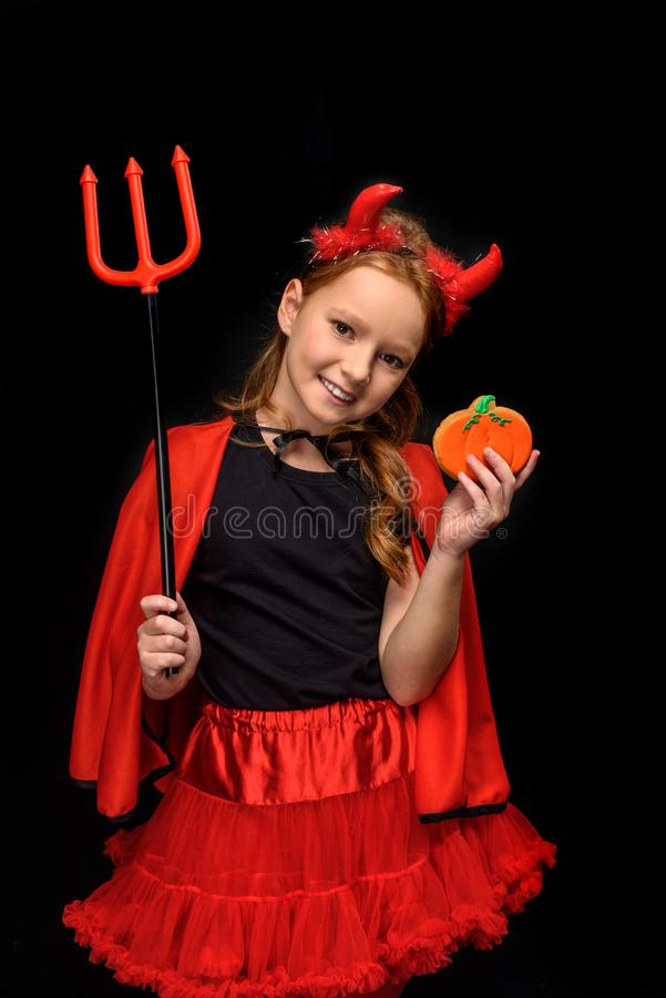 Devil with pitchfork and cookie stock photo