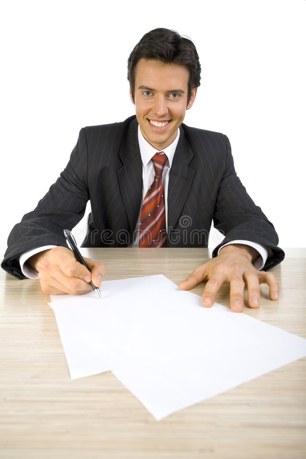 Devil's advocate. Smiling, handsome businessman. Seating behind desk, writing something. Looking at camera. White background, front stock image