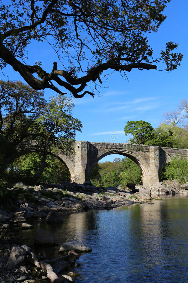Devil`s Bridge, Kirkby Lonsdale, Cumbria. Looking up the River Lune at Kirkby Lonsdale to the famous Devil`s Bridge which once carried the main road across the royalty free stock image