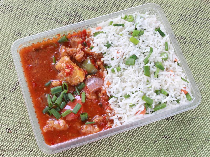 Devil`s chicken with rice combo takeaway. Indian hot Spicy chicken curry with fried rice combo takeaway royalty free stock image