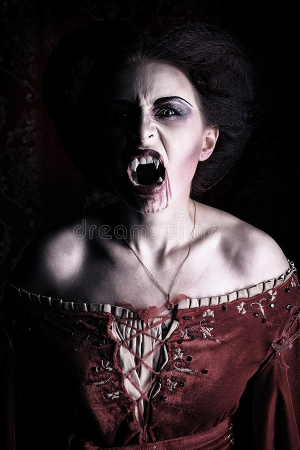Devil woman. Close-up portrait of a bloodthirsty female vampire stock photo