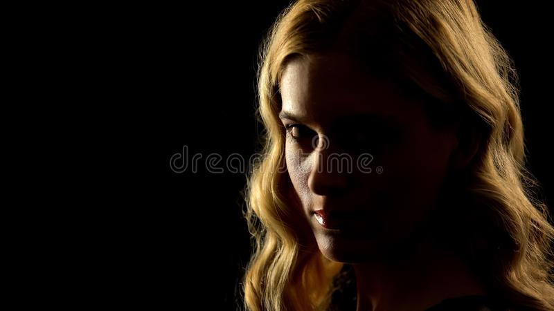 Devil woman looking at camera, black background, paranormal mystery, white eyes stock images
