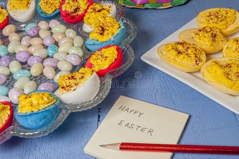 Deviled ägg, påsk färgade, candypost det anmärkningen arkivfoton