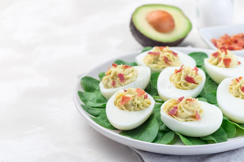Deviled eggs stuffed with avocado, egg yolk and mayonnaise filling, garnished with bacon, on spinach leaves, horizontal copy space. Deviled eggs stuffed with stock image