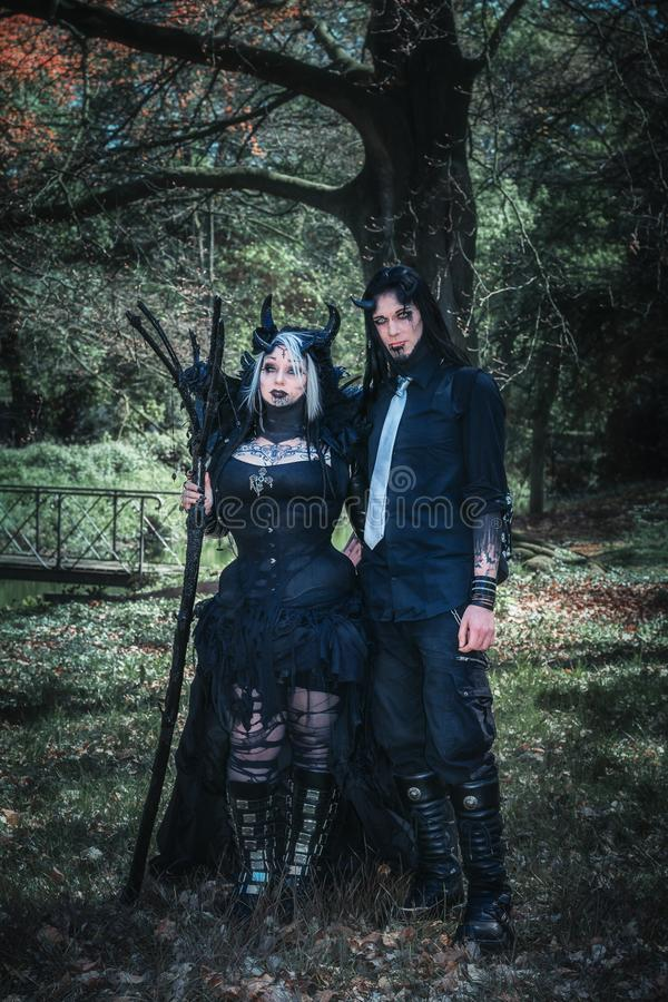 Devilish couple poses in the forest during the Elf Fantasy Fair. April 19, 2014, Haarzuilens, The Netherlands: Devilish couple poses in the forest during the Elf royalty free stock photos