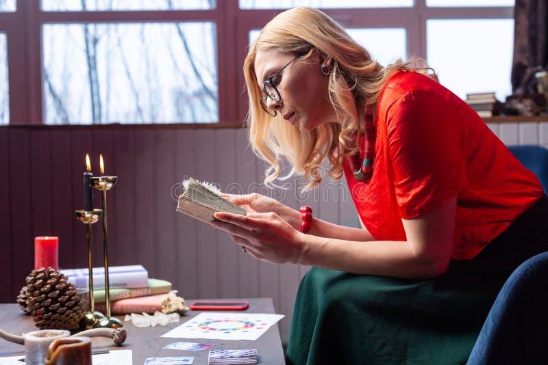 devin féminin aux cheveux blonds se sentant occupé tandis que livre de lecture pour des magiciens photos stock