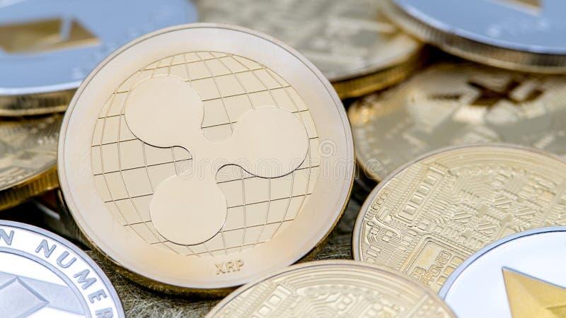 Devise d'or de Ripplecoin en métal physique au-dessus d'autres pièces de monnaie Pi?ce de monnaie d'ondulation photo stock