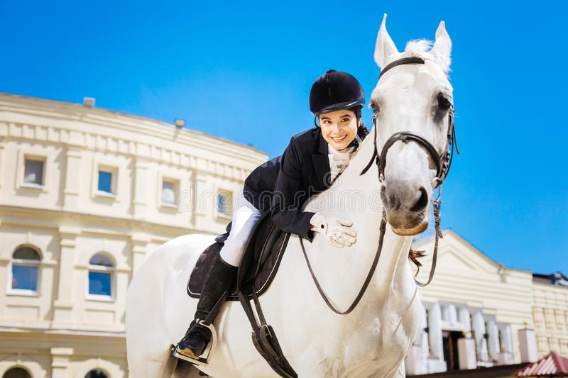 Black-eyed beaming female rider leaning on her devoted white horse royalty free stock photos
