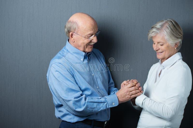 Devoted senior couple holding hands stock image
