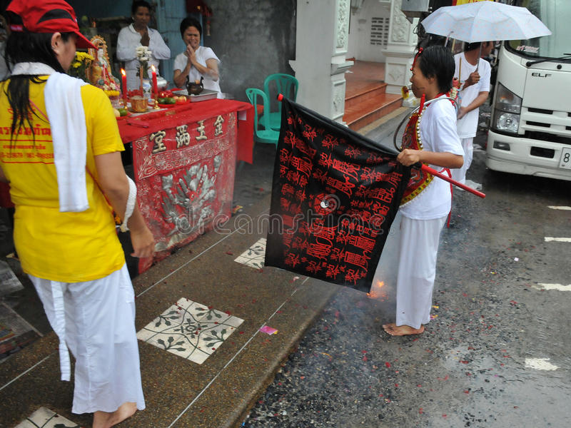 Devotee Blesses a Family during a Taoist Festival. A female Taoist devotee blesses a family at their home during a procession of the Nine Emperor Gods Festival royalty free stock image