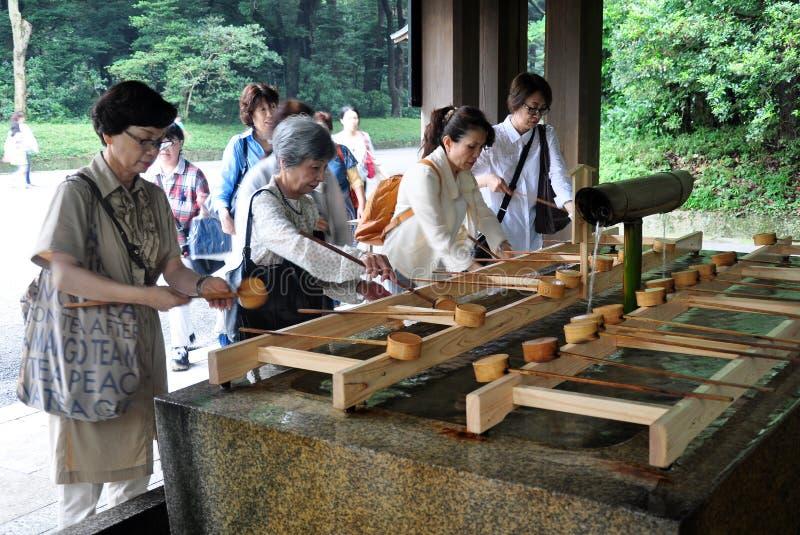 Devotos que realizan harai antes de la adoración en Meiji Shrine, Tokio, Japón fotografía de archivo