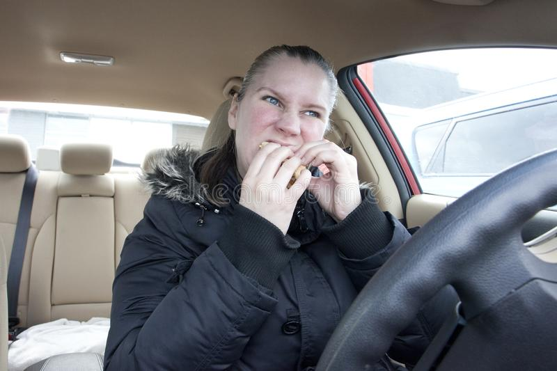 Devouring fast food sandwich. A woman hungrily eats fast food in her car stock photography