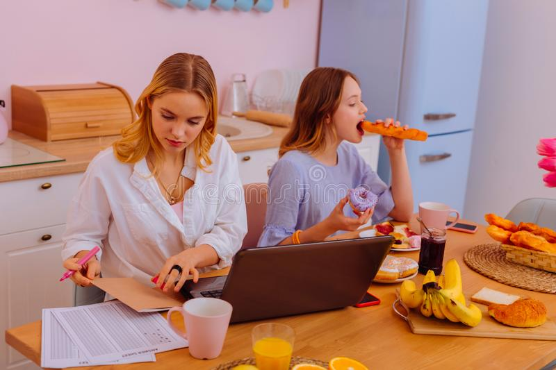 Freelance writer finishing project while sibling devouring sweets. Devouring sweets. Blonde-haired freelance writer finishing project while sibling devouring stock photos