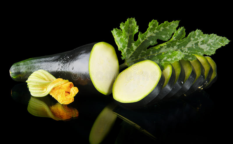 Dewed zucchini cut into slices with flower and leaf on black. Mature dewed zucchini cut into slices with flower and courgette leaf on black background stock photos