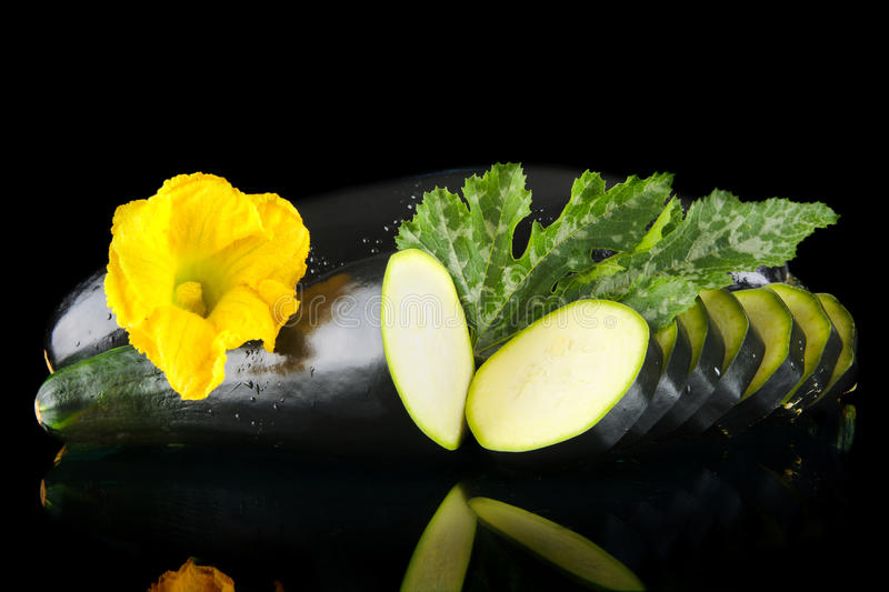 Dewed zucchini cut into slices with flower and leaf on black. Mature dewed zucchini cut into slices with flower and courgette leaf on black background royalty free stock images