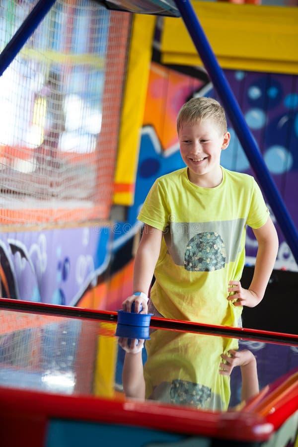 Dez anos feliz e menino sorrindo idoso que joga o hóquei do ar na sala de jogos das crianças fotos de stock royalty free