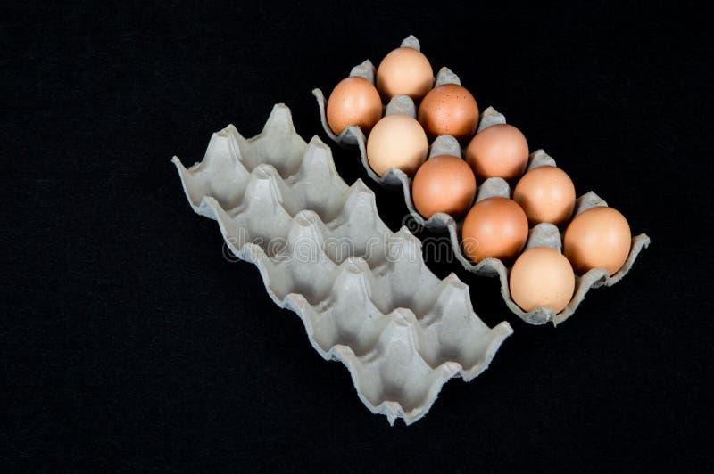 Dez ovos da galinha em uma caixa da caixa e em uma caixa vazia da caixa isoladas no fundo preto da esteira fotografia de stock