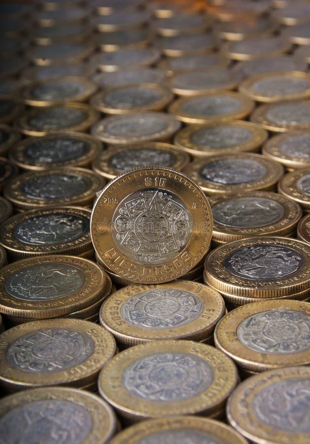 Dez pesos mexicanos inventam sobre mais moedas alinhadas e empilhadas fotos de stock royalty free