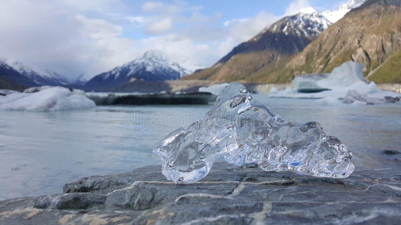 Deze foto wordt genomen in Onderstel Cook Glacier in Zeeland Een hand rekt zich uit uit om een stuk van ijs te houden Het ijs is  royalty-vrije stock foto
