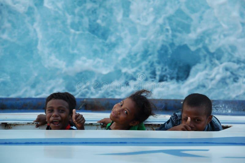 Deze 3 het westen papuan kinderen schreeuwen tot het dek aangezien het wervelende overzees onder hen op de boot is royalty-vrije stock foto