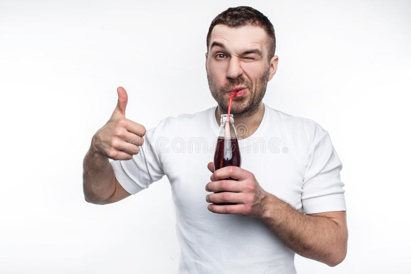 Deze mens houdt zeer van snel voedsel en zoete dranken ook Hij drinkt cokes van de fles met genoegen ook stock foto's