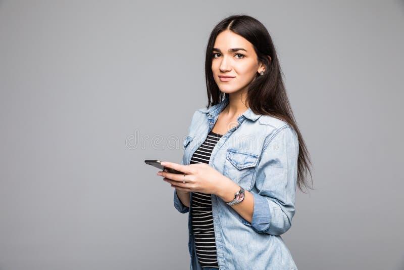 Deze mobiele telefoon is voor slimme mensen Mooie jonge vrouw die mobiele telefoon houden en camera bekijken terwijl status tegen royalty-vrije stock foto