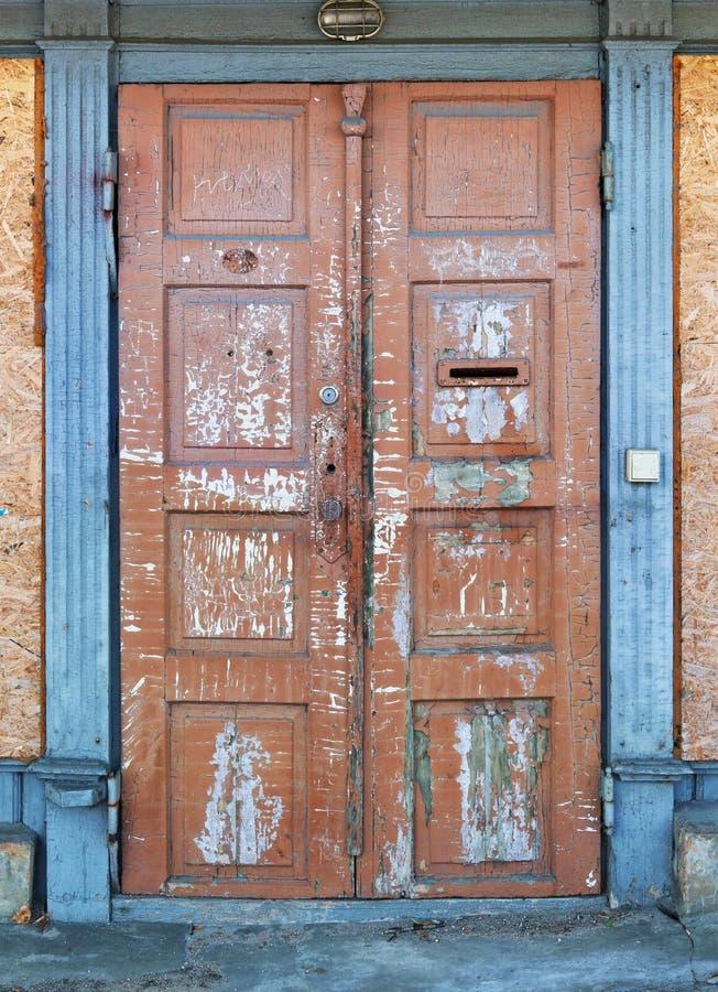 Deze vlokkige gebarsten rode deur en blauw deurkader royalty-vrije stock foto