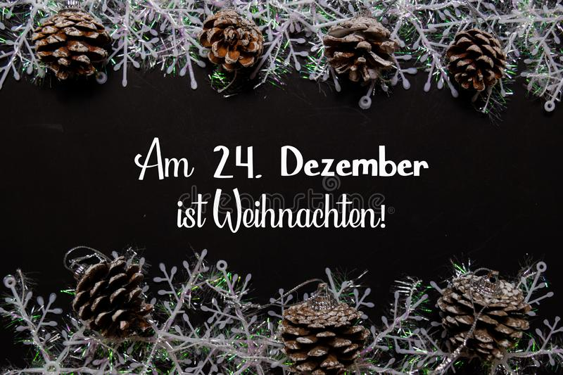 Am 24. Dezember Ist Weihnachten Text isolated on black background. It means Merry Christmas. Frame of Christmas Decoration stock photo