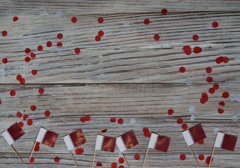 18. Dezember Unabhängigkeitstag Katars Mini-Flaggen auf Holzboden mit Papierfass glücklicher Tag des Patriotismus stockfotografie