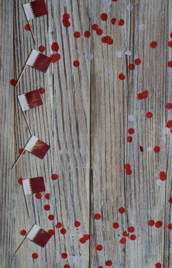 18. Dezember Unabhängigkeitstag Katars Mini-Flaggen auf Holzboden mit Papierfass glücklicher Tag des Patriotismus stockfotos