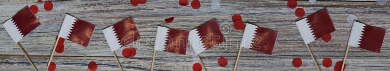 18. Dezember Unabhängigkeitstag Katars Mini-Flaggen auf Holzboden mit Papierfass glücklicher Tag des Patriotismus lizenzfreie stockfotos