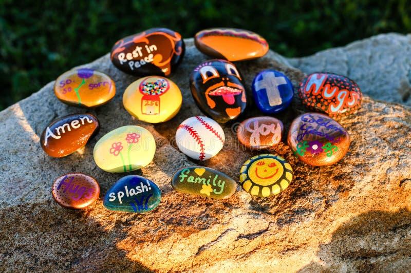 Dezesseis pintaram rochas em um pedregulho no sol da tarde foto de stock