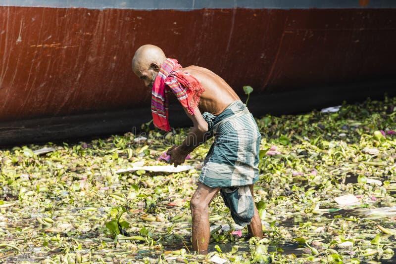 Dhaka, Μπανγκλαντές, στις 24 Φεβρουαρίου 2017: Ηληκιωμένος που ψάχνει το ανακυκλώσιμο υλικό σε έναν ποταμό στοκ εικόνες με δικαίωμα ελεύθερης χρήσης