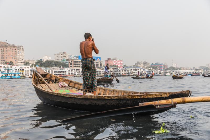 Dhaka, Bangladesh: Boatman washing himself on a wooden boat down Buriganga Ganmges River in Old Dhaka. Large white ferry royalty free stock photo