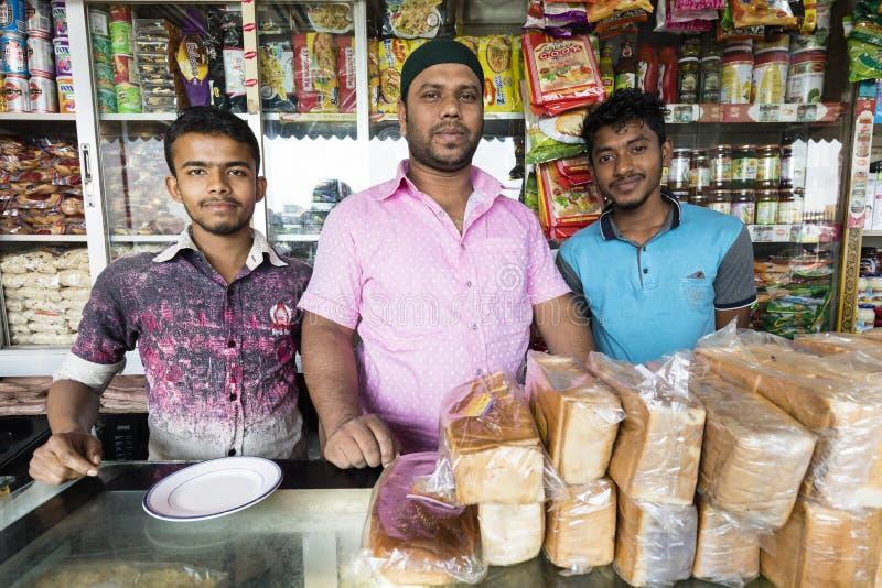 Dhaka Bangladesh, Februari 24 2017: Tre salespeople poserar proudly i deras shoppar i Dhaka royaltyfria foton